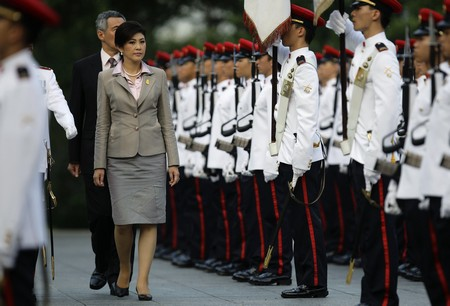 Thai PM Yingluck inspects an honour guard with her Singaporean ...